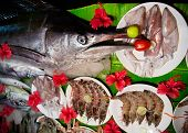 Different raw fish calamari and prawns in flowers on banana leaf on street market in India poster