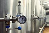 Craft beer brewing equipment in brewery. Metal tanks, alcoholic drink production. Facilities in modern interior of brewery. Manufacturable process of brewage. Mode of beer production. Tank indicator. poster