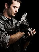 portrait of young soldier reloading his gun against a black background poster