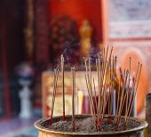 Burning Incense in Chinese Buddhist Temple background, material offering of traditional Mahayana Buddhist devotional practices for accumulation of merit. Religion, Travel Asia, Culture, Symbol concept poster