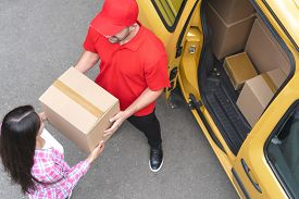 Courier In Red Uniform Takes The Delivery Package From Woman S Hands. Brunette Woman Takes Her Parce