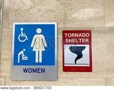 The Women's Restroom And Tornado Shelter Signs Directing People To The Shelter