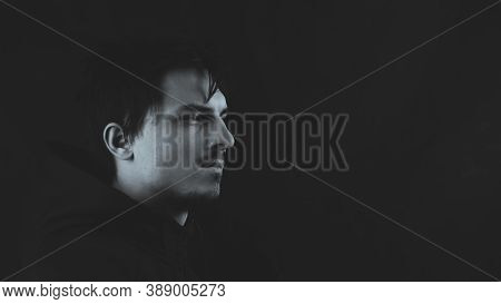 Profile View Of Young Man In The Dark. Male Portrait