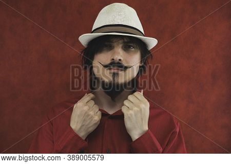 Young Man With Hat In Red Shirt On The Red Background. Male Portrait