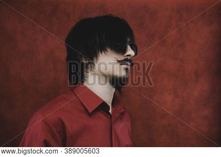 Young Man With Glasses In Red Shirt On The Red Background. Male Portrait