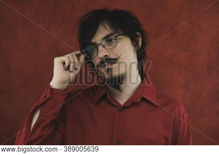 Man With Eyeglasses In Red Shirt On The Red Background. Male Portrait