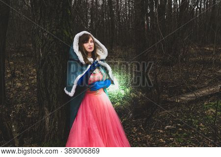Sorceress Casting A Spell. Woman In Fantasy Costume With Cape Leaned Against A Tree. Magic Autumn