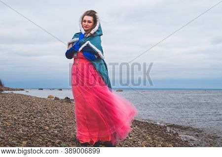 Woman In Costume With Cape. Adult Woman With A Mantle Standing On The Seashore