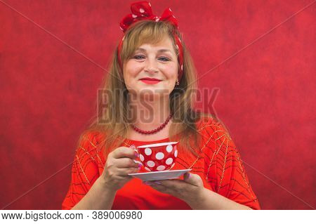 Woman In Red Posing On The Red Background. Spotted Cup With Saucer In The Hands. Funny Style