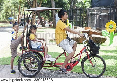 Happy Family Trip In Holiday, Father Riding A Tricycle For His Son And Daughter To Sit.