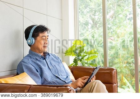 Senior Asian Grandfather Enjoy And While Listening Music Or Watch Movie From Wireless Headphone That