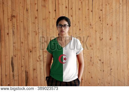 Woman Wearing Algeria Flag Color Shirt And Standing With Two Hands In Pant Pockets On The Wooden Wal