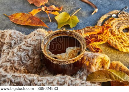 Autumn, Fall Leaves, A Hot Steaming Cup Of Coffee And A Warm Scarf Against The Background Of A Blue