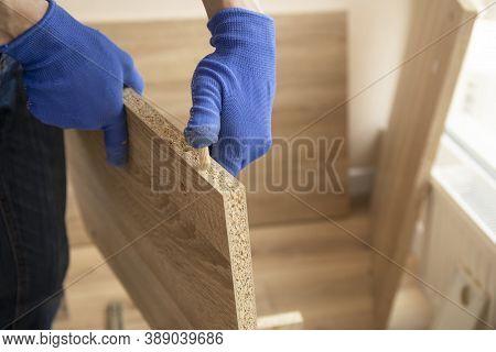 Professional Carpenter Master Assembling The Furniture In Blue Gloves