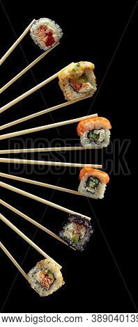 Fresh Tasty Sushi In Wooden Chopsticks On A Black Background. Copy Space.