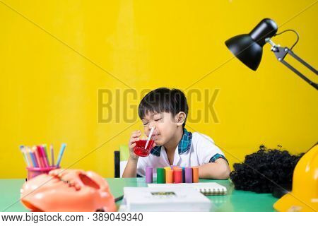Boy Was Sleepy While Drinking Sweet Water, At The Homework Desk.