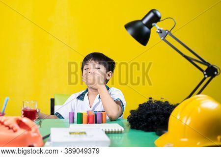 Boy Was Sleepy While Doing Homework, On The Table There Are School Supplies.