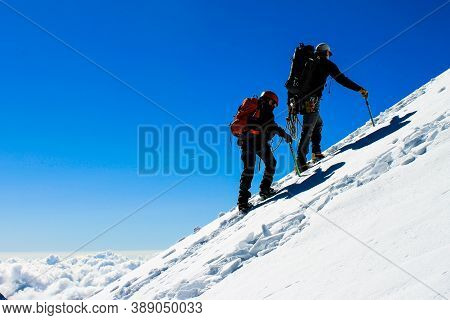 Father And Son Mountaineering Together In The Swiss Alps