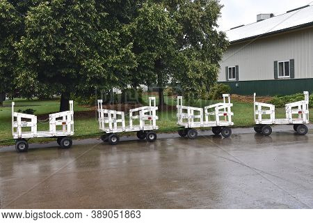 Mini Hayracks Used As People Movers Are Parked During Rain At A Fairgrounds Festival.