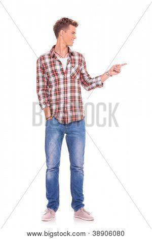 full length photo of a casual young man looking and pointing in a side direction and holding his other hand in his pocket