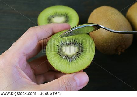 Closeup Hand Holding Cut Kiwifruit Scooping With A Spoon On Black Background