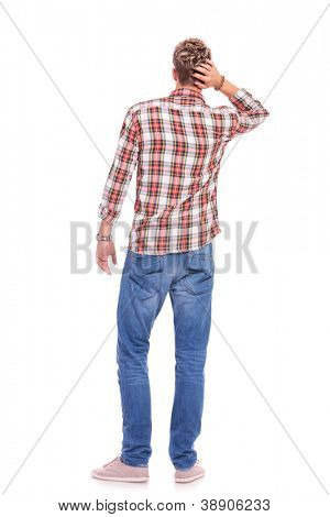 back view of a confused young casual man with his hand on the back of his head. isolated on white