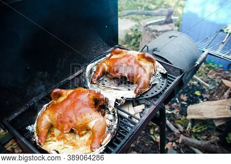 Whole Turkey Grilled Outdoors. Two Roasted Turkeys In Sauce