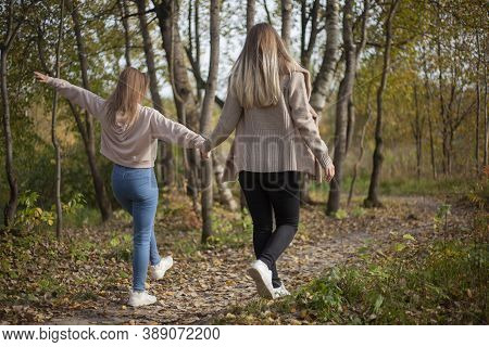 The Girls Are Holding Hands. Friends Are Walking In The Autumn Forest. Two Girls Happily Walk Throug