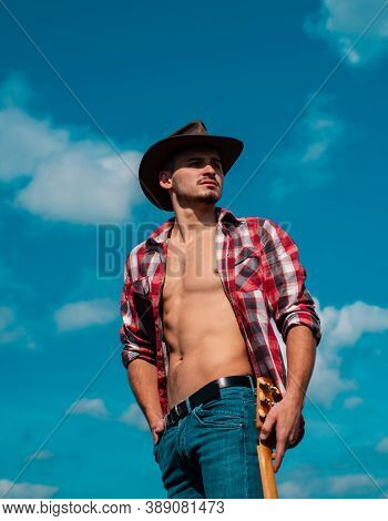 Cowboy Couture. Portrait Of Young Man Wearing Cowboy Hat And Looking Up While Standing Against Sky B