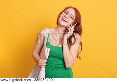European Red Haired Woman Laughs Carefree While Talks On Mobile Phone, Hears Something Funny Or Very