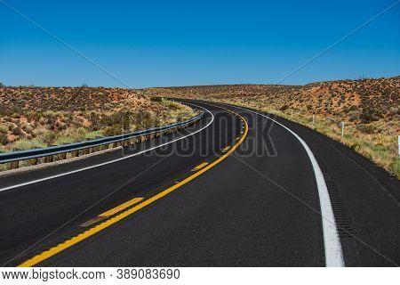 American Roadtrip. Asphalt Road Straight Through The Field With Blue Sky In Autumn