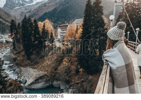 Teenage girl traveler wrapped in warm blanket standing on bridge and looking at river over mountains view. Student spending autumn or winter holidays in european places.