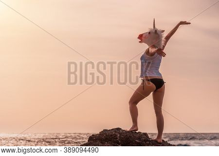 Unusual Woman In White T-shirt And Black Swimsuit With Unicorn Head Mask Dancing By The Sea On The B