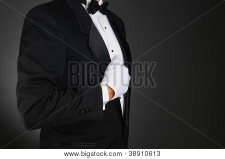 Perfil de un hombre vestido con un esmoquin y guantes blancos, sosteniendo su solapa en primer plano. Formato horizontal en un