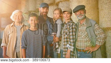 Portrait Of Happy Caucasian Family Of Three Generations Standing Outdoor At Hay Stocks And Smiling T