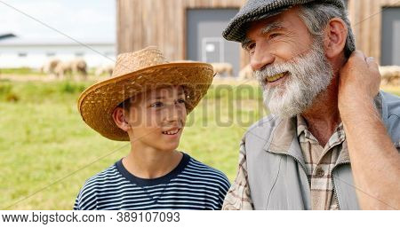 Senior Grandfather With Beard Standing At Field With Small Nice Grandson And Telling And Preaching.