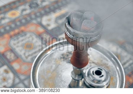 Embers On Hookah Bowl With Smoke Against Traditional Arabic Style Carpet
