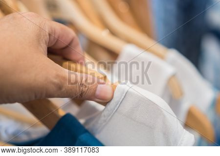 Customer Or Shopper Choosing Clothes On Wooden Hangers In Shelf Fashion For Sale Shopfront Store Col