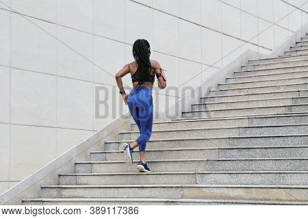 Fit Young Woman In Blue Leggings Running Up The Stairs, View From The Back