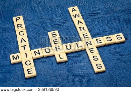 Practice mindfulness and self awareness - inspirational crossword in ivory letters against blue textured paper, personal development concept