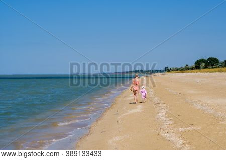 Rear View Of A Mother And A Baby Girl Walking Along A Deserted Sandy Sea Beach Along The Surf Agains