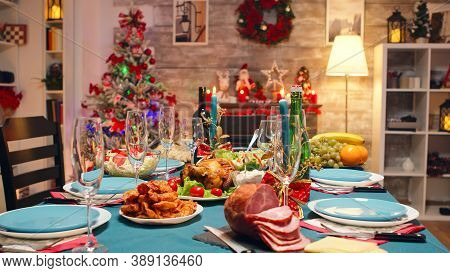 Christmas Table Decoration With Burning Candles And Traditional Food. Xmas Celebration In Decorated