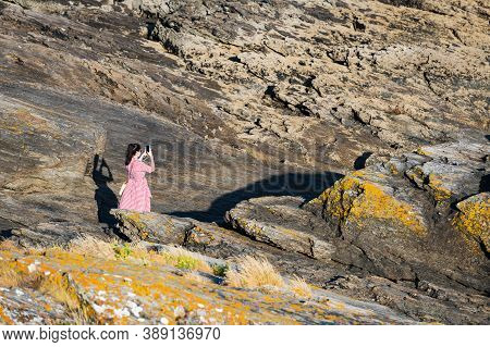 Portonovo, Spain - August 15, 2020: A Young Woman Takes A Picture With Her Smartphone While Enjoying