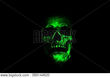 Halloween Human Skull. A Spooky Monstrous Human Skull Isolated on Black. Green light on a human skull in the night.