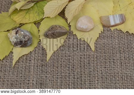 Four Semi-precious Stones Of Septaria, Landscape Jasper, Yellow Quartz, Agate Lie On Jute Fabric On