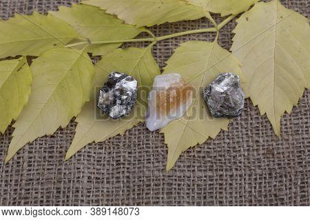 Three Semi-precious Stones, Two Phlogopites And Citrine, Lie On A Jute Fabric On Autumn Yellow Leave