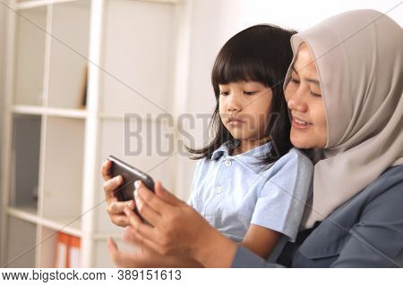 Asian Muslim Mom And Little Baby Girl Daughter Learning Online Or Watching Videos On Tablet Phone, H