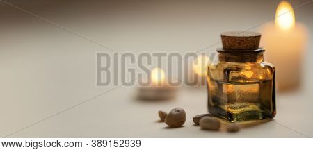 Tranquil And Concise Spa Composition With Oil Flask, Stones And Candles. Copy Space