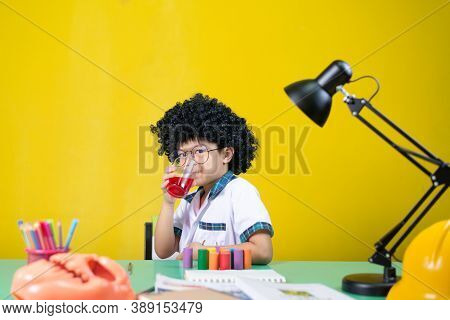 Children Wearing Wigs Funny Gestures Are Drinking Sweet Water, At The Homework Desk.