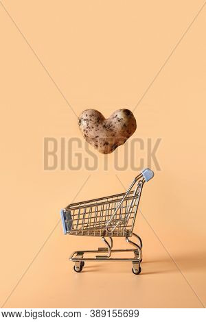 Abnormal Potato In Shape Of Heart Flying Into Grocery Cart On Natural Beige Background. Concept Love
